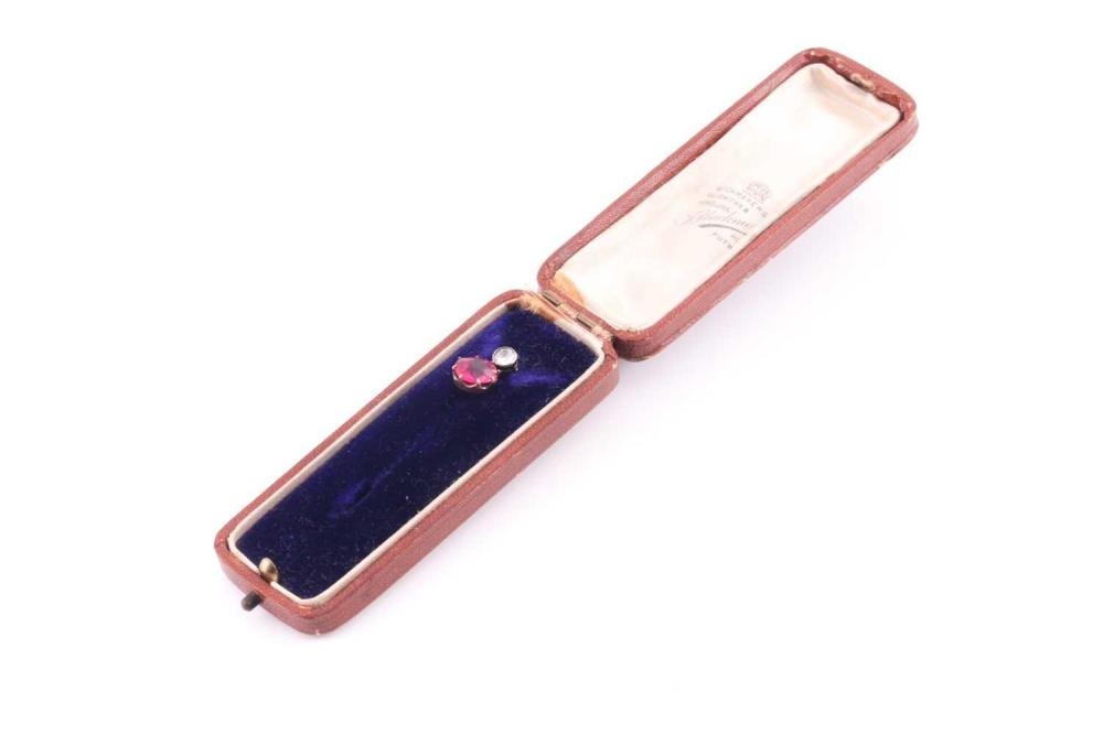 A yellow metal and diamond tie pin, set with an old-cut diamond, approximately 4 mm diameter, suspended with a red paste stone, pin unmarked, in an antique tie pin box.