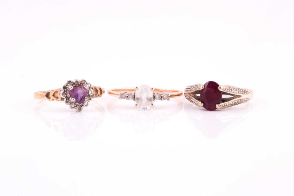 A single stone ruby ring; the oval cut ruby claw mount to bifurcated diamond set shoulders; an amethyst and diamond heart-shaped cluster ring and one further gem set ring, all in 9 carat gold mounts. (3) 6.33 grams