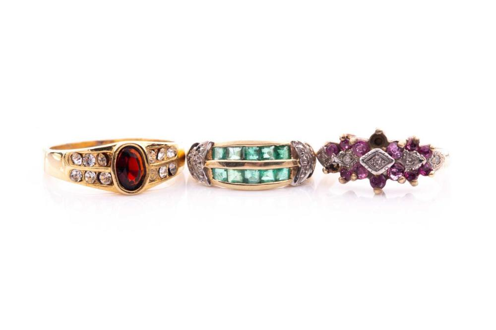 A 9 carat gold ruby and diamond triple cluster ring, (two rubies deficient) an emerald and diamond two row ring, and a garnet and clear stone ring (unmarked), 7.7 grams combined. (3)