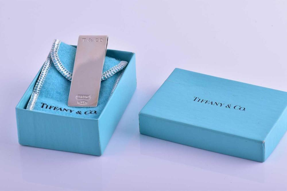 Tiffany & Co. A silver money clip, marked 1837 and 925, engrave T & Co, approximately 6 cm long, in original pouch and gift box.