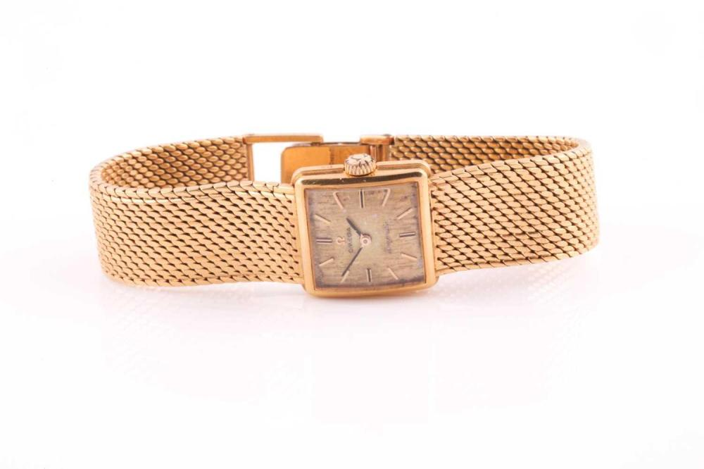 Omega. A lady's 18 carat gold 'Ladymatic' wristwatch; the brushed square dial with baton indices; numbered manual wind movement; movement case and dial signed. Integral woven mesh link bracelet with deployant clasp; dial 19mm diam. Gross weight...