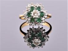 An 18 carat yellow gold, diamond, and emerald floral cluster ring centred with round cut diamond of approx. 0.33 carats, surrounded by round cut emeralds and diamonds. Size: N
