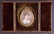 An early 19th century portrait miniature of a young lady wearing a blue gown, c. 1810, watercolour on ivory, within green velvet lined brown leather travelling case. Portrait, H: 6cm W: 5cm