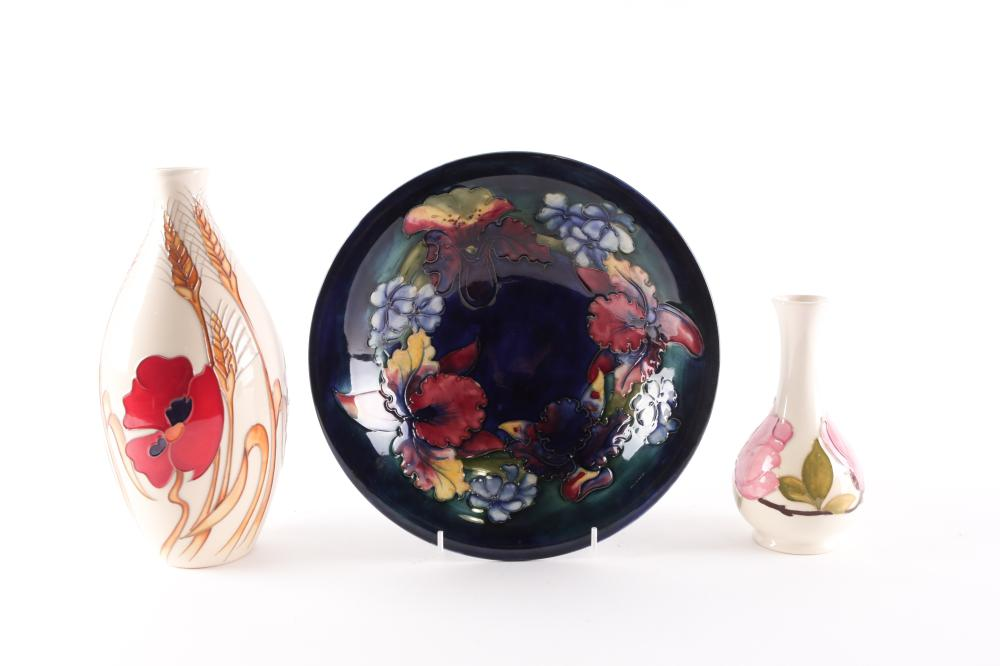 A Walter Moorcroft Orchid pattern bowl, mid 20th century, on a shaded blue - green ground, 25cm dia, a Moorcroft Harvest Poppy vase designed by Emma Bossons, 24.5cm; and a small Moorcroft magnolia pattern vase, 15.5cm
