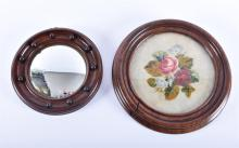 A small convex mirror in a wooden frame