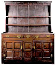 An 18th century Welsh oak dresser with three drawers above two panelled cupboard doors opening to