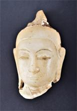 An Indian alabaster Buddha head fragment with serene expression, lengthened earlobes and topknot,