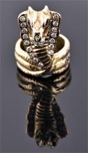 An unusual yellow metal and diamond snake ring in the form of a rearing cobra, the hood set with