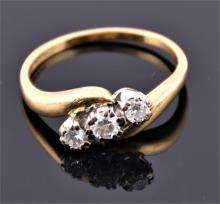 An 18ct yellow gold and diamond three stone crossover ring set with three round cut diamonds of