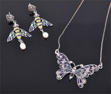 A silver, marcasite, and plique- à-jour style butterfly pendant necklace decorated in blue and