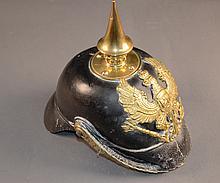 Casque à pointe prussien, modèle 1867  Bombe de casque 1860 modifiée d'origine en 1867, marquée du 11e régiment d'infanterie prussien, jugulaire à écailles, et pointe perlée  Eclat de schrapnel sur la visière avant