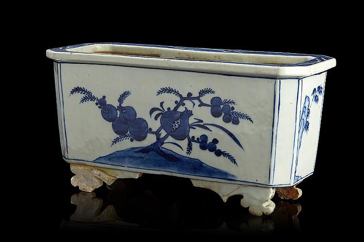 CHINE Jardinière en porcelaine de forme rectangulaire à pans coupés reposant sur quatre pieds, décorée en bleu sous couverte de grenades sur deux faces et alternées de bambous sur des rochers. Fin XIXe siècle. Dim. : 17 x 33 x 13 cm. (deux pieds