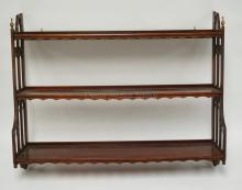 MAHOGANY 3 TIER HANGING SHELF WITH CUTWORK SIDES, BRASS FINIALS, AND SCALLOPED SHELF SKIRTS. 32 INCHES WIDE. 25 1/2 INCHES HIGH.