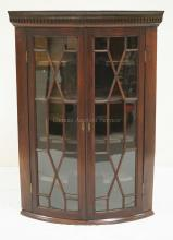 ANTIQUE MAHOGANY HANGING CORNER CABINET WITH INDIVIDUALLY PANED DOORS AND DENTAL MOLDING. 40 INCHES HIGH. 28 3/4 INCHES WIDE.