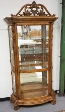 CARVED CURIO CABINET WITH GLASS SHELVES, A MIRRORED BACK, AND A LIGHTED INTERIOR. LOADING DOORS ON EACH SIDE. 48 INCHES WIDE. 90 INCHES HIGH.
