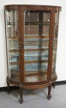 OAK CHINA CABINET WITH A MIRRORED BACK AND GLASS SHELVES. CARVED DECORATIONS INCLUDING PAW FEET. 62 1/2 INCHES HIGH. 39 1/4 INCHES WIDE.