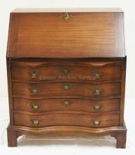 MAHOGANY SLANT FRONT DESK WITH A SERPENTINE FRONT AND A COMPARTMENTED INTERIOR. 41 1/2 INCHES HIGH. 38 1/4 INCHES WIDE.