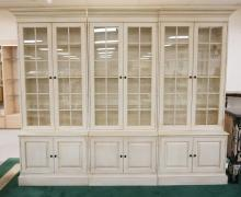 ETHAN ALLEN 3 SECTION CABINETS WITH BLIND DOOR BASES AND GLASS PANE DOORS WITH GLASS SHELVES AND LIGHTED INTERIORS FOR THE TOP SECTIONS. 86 1/2 INCHES HIGH. 108 INCHES WIDE.