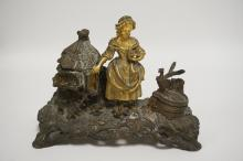 FIGURAL GOLD GILT AND PATINATED BRONZE INKWELL IN THE FORM OF A GIRL WITH CHICKENS BY A CHICKEN COOP. 9 1/2 INCHES LONG. 4 3/8 INCHES DEEP. 7 INCHES HIGH.