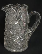DEEP BRILLIANT CUT GLASS PITCHER W/ DEEP NOTCHES CUT IN THE APPLIED HANDLE. 8 1/4 IN H