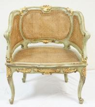 CARVED, GILT AND PAINT DECORATED BARREL BACK FRENCH STYLE CHAIR W/ CANED SEAT AND DOUBLE CANED BACK AND SIDES. 27 1/2 IN WIDE, 31 1/2 IN H