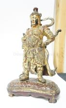GILT AND PAINTED ORIENTAL FIGURE MOUNTED ON A WOODEN BASE. 11 3/4 IN H