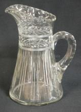 CUT GLASS PITCHER W/ 2 HORIZONTAL BANDS OF LEAVES AND VERTICAL LINES. THUMBPRINT CUTS ON THE HANDLE. 10 1/4 IN H