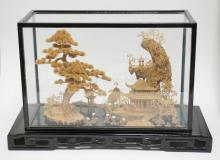 LARGE ELABORATE CORK CARVING W/ TREE, BRIDGE, BUILDING AND WADING BIRDS. MOUNTED ON A CARVED WOODEN BASE W/ GLASS AND WOOD COVER. 21 1/2 IN X 9 IN BASE. 13 3/4 IN H