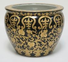 ASIAN PLANTER IN BLACK AND GOLD DECOR ON THE EXTERIOR AND FISH ON THE INTERIOR. 14 1/2 INCHES WIDE. 11 INCHES HIGH.