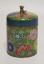 CLOISONNE COVERED JAR DECORATED WITH FLOWERS AND A FOO DOG FINIAL. 6 1/2 INCHES HIGH.