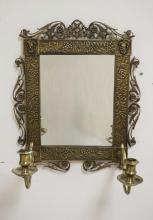 BRASS WALL MIRROR/SCONCE WITH 2 CANDLE ARMS. DECORATED WITH FACES, LEAVES, AND FLOWERS. 15 1/4 X 13 INCHES.
