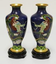 PAIR OF CLOISONNE VASES DECORATED WITH DRAGONS. EACH WITH A CARVED WOODEN BASE. 11 3/4 INCHES HIGH.