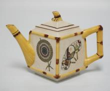 JAPANESE PORCELAIN TEAPOT MADE FOR THE METROPOLITAN MUSEUM OF ART. DECORATED WITH FIGURES, BIRDS, AND FANS. CRAZED. 5 1/4 INCHES HIGH.