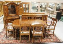 9 PIECE JACOBEAN STYLE DINING ROOM SET INCLUDING A TABLE WITH ONE LEAF, 6 CHAIRS, CHINA CABINET, AND A SIDEBOARD. MADE BY HERRMANN FURNITURE COMPANY, NY. ONE CHAIR HAS A REPAIRED BACK SUPPORT.