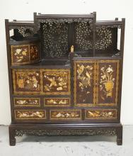 ASIAN LACQUERED CABINET WITH CHINOISERIE DECORATION IN CARVED STONE AND PAINT WITH SCENES OF FIGURES, BIRDS IN A NEST, FLOWERS, ETC. TRIMMED WITH INTRICATELY CARVED FILAGREE. HAS SOME LOSSES. 50 1/2 INCHES WIDE. 58 INCHES HIGH.