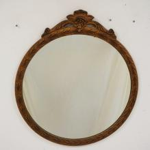 ROUND MIRROR IN A GOLD GILT FRAME WITH A CARVED CREST. 26 1/2 INCH DIA.
