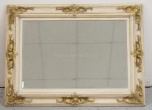 BEVELED MIRROR IN A WOODEN FRAME WITH APPLIED CARVED GOLD GILT ACCENTS. 46 3/4 X 36 INCHES.
