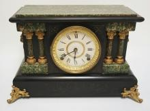 SETH THOMAS VICTORIAN MANTLE CLOCK WITH FAUX MARBLE DECORATION AND LION HEADS. 16 3/4 IN WIDE