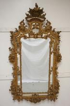 ANTIQUE GILTWOOD MIRROR WITH AN ORNATE OPENWORK FRAME AND A DEEP CREST. 74 X 40 INCHES.