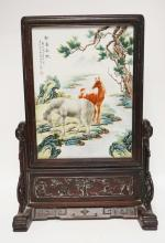 HAND PAINTED ASIAN PORCELAIN PANEL DEPICTING HORSES BY A STREAM WITH TREES. HARDWOOD FRAMED WITH A CARVED BASE HAVING DECORATIONS INCLUDING HORSES, BIRDS, AND TREES. MARKED WITH CHARACTERS AND A RED CHOP MARK. 27 3/4 INCHES HIGH. 19 1/2 INCHE WIDE.
