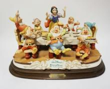 WALT DISNEY'S *SNOW WHITE AND THE SEVEN DWARFS HAVING DINNER* FIGURAL PORCELAIN GROUP BY LAURENZ . COMES WITH ORIGINAL WOODEN BASE AND PAPERWORK. 18 INCHES WIDE.