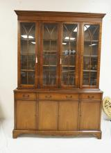 MAHOGANY CHINA CABINET WITH A CARVED BAND ALONG THE CREST. INDIVIDIALLY PANED. 83 1/2 INCHES HIGH. 59 INCHES WIDE.