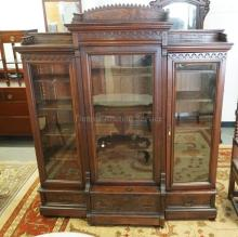 VICTORIAN WALNUT BOOKCASE WITH GLASS DOORS, CARVED ACCENTS, AND BURLED PANELS. 63 INCHES WIDE. 72 INCHES HIGH.