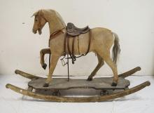 LARGE HIDE COVERED CHILDS ROCKING/ROLLING HORSE. 38 INCHES HIGH. 59 1/2 INCHES LONG.