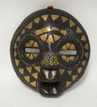CARVED WOODEN TRIBAL MASK DECORATED WITH BEADS AND BRASS. ONE BRASS TRIANGLE MISSING.