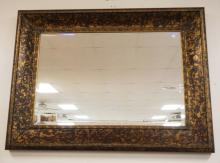BEVELED WALL MIRROR IN A MOTTLED BLACK AND GOLD GILT FRAME. 47 1/2 X 35 3/4 INCHES.