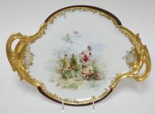 HAND PAINTED PORCELAIN TRAY OF A WOMAN IN A PERIOD FRENCH DRESS WITH A BASKET OF FLOWERS NEAR BEEHIVES AND CHERUBS. 17 1/4 IN X 12 1/4 IN. ARTIST SIGNED B. WALLACE.