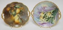 2 LIMOGES HAND PAINTED HANDLED CAKE PLATES- ONE W/ ORANGES, ONE DAFFODILS. BOTH ARTIST SIGNED. 10 3/4- 11 IN