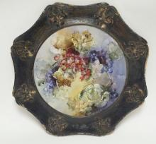 HAND PAINTED PORCELAIN PLAQUE IN AN EBONIZED. OAK FRAME W/ RELIEF FLOWERS. GRAPEVINES. PLAQUE IS 17 3/4 IN,  27 IN W/ FRAME