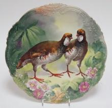 HAND PAINTED PORCELAIN CHARGER WITH A PAIR OF QUAIL AND A FOLIATE AND FLOWER BORDER. UNMARKED PORCELAIN. ARTIST SIGNED DUMONTEIL. 14 IN DIA.